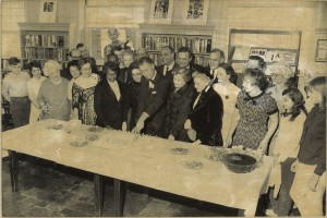 Erma Parham in the Grand Street Library in 1959. Cutting the cake is Danby Osborn, head of the Board of Trustees. Samuel L. Parham, Jr. is visible behind Erma.